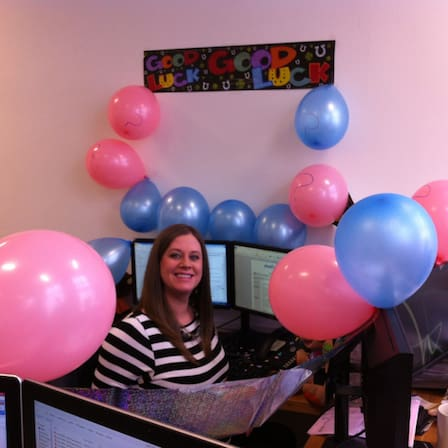 Shot of Jayne in Physio.co.uk office with pink and blue balloons and a banner on the wall saying good luck.