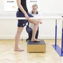 Side shot of a patient placing their left leg on a wooden box while holding on to two beams with a neurological therapist placing their left hand on the patients left knee.