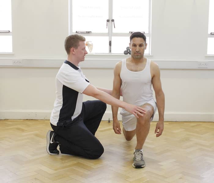 Wide shot of man knelt down on one knee with therapist by the side of man holding the mans forward knee.