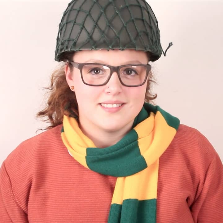 Portrait of Bethany wearing army helmet and green and yellow patterned scarf