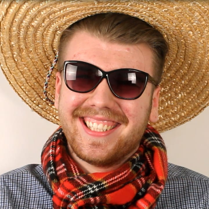 Portrait of Connor wearing sombrero and checkard scarf