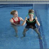 Wide shot of female in swimming pool holding a large ring in front of her with a physiotherapist holding on to females roght elbow.